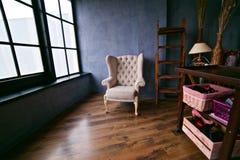 一把扶手椅子在一间黑暗的现代被设计的屋子 免版税图库摄影