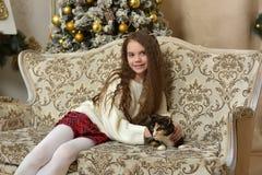 一把扶手椅子的女孩有在圣诞节的一只猫的 免版税图库摄影