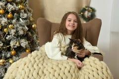 一把扶手椅子的女孩有在圣诞节的一只猫的 免版税库存图片