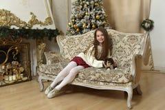 一把扶手椅子的女孩有在圣诞节的一只猫的 库存照片