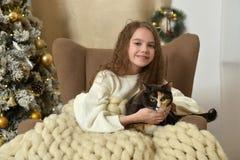 一把扶手椅子的女孩有在圣诞节的一只猫的 图库摄影