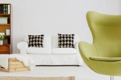 一把扶手椅子的著名形状在一个现代客厅 图库摄影