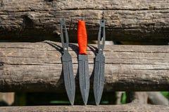 一把投掷的刀子的照片在木背景的 不锈的斯特 图库摄影