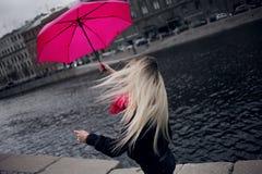 一把明亮的桃红色围巾,胶靴和伞的美丽的年轻和愉快的白肤金发的妇女走在一个多雨城市的 库存照片