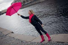一把明亮的桃红色围巾,胶靴和伞的美丽的年轻和愉快的白肤金发的妇女走在一个多雨城市的 免版税图库摄影