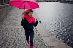 一把明亮的桃红色围巾,胶靴和伞的美丽的年轻和愉快的白肤金发的妇女走在一个多雨城市的 图库摄影