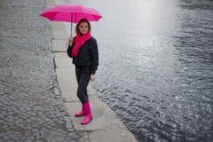 一把明亮的桃红色围巾,胶靴和伞的美丽的年轻和愉快的白肤金发的妇女走在一个多雨城市的 免版税库存照片