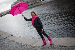 一把明亮的桃红色围巾,胶靴和伞的美丽的年轻和愉快的白肤金发的妇女走在一个多雨城市的 免版税库存图片