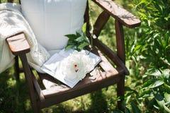 一把木与中介子的椅子在庭院里和书 库存图片