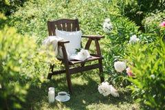 一把木椅子在庭院里和一杯茶 库存照片
