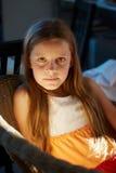 一把柳条扶手椅子的女孩 免版税库存照片
