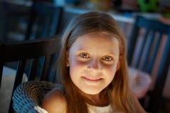 一把柳条扶手椅子的女孩 免版税库存图片