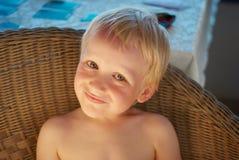 一把柳条扶手椅子的男孩 库存图片