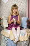 一把椅子的女孩与书 免版税库存图片