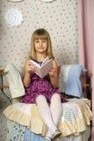 一把椅子的女孩与书 免版税库存照片