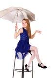 一把椅子的女孩与伞 库存照片
