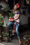 一把椅子的女孩与花 免版税库存图片
