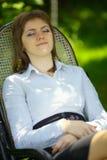 一把椅子的妇女在庭院里 库存图片
