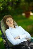 一把椅子的妇女在庭院里 库存照片