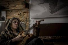 一把椅子的年轻人与手工制造吉他 免版税库存照片