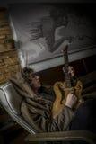 一把椅子的年轻人与手工制造吉他 库存图片