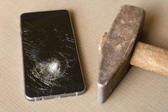 一把残破的手机和锤子在灰色背景 免版税库存照片