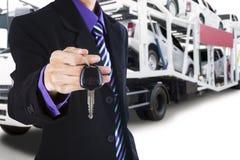 给一把汽车钥匙有拖车背景的司机 图库摄影
