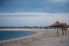 一把沙滩伞的剪影在日落的 在海运的日落 免版税库存图片