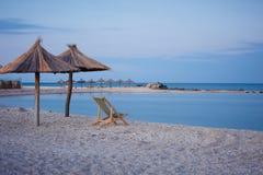 一把沙滩伞的剪影在日落的 在海运的日落 库存图片