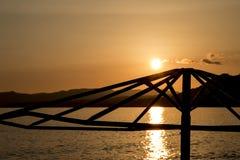 一把沙滩伞的剪影在日落的在罗得岛海岛上  库存照片