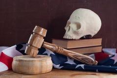 一把法院锤子和一块头骨在美国的旗子的背景, 免版税库存图片