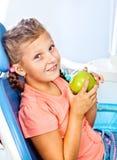 一把牙齿椅子的愉快的女孩 免版税库存图片