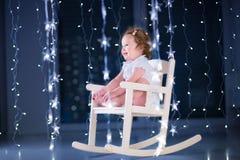 一把白色摇椅的美丽的矮小的小孩女孩在有圣诞灯的一个暗室 库存图片