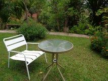 一把白色椅子和表在庭院里 库存图片