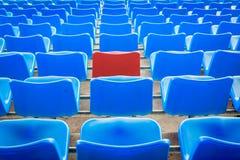 一把空的红色椅子, arounded由蓝色椅子在橄榄球Stad 库存照片