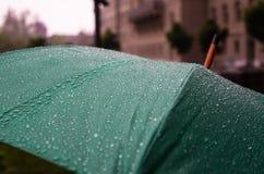 一把绿色伞的接近的看法有雨小滴的和在焦点外面 库存照片