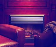 一把舒适的舒适内部壁炉和舒适扶手椅子在livin 库存照片