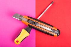 一把螺丝刀和切削刀在桃红色和红色背景 免版税库存图片