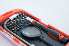 一把螺丝刀的红色箱子有一套的准确的位与放大镜一起使用 库存图片