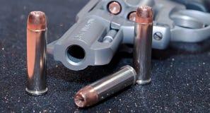 一把被装载的左轮手枪用在它旁边的三枚子弹 免版税库存照片
