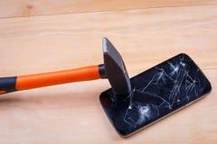 一把重的锤子击中智能手机的屏幕并且捣毁它 在一个木背景 特写镜头 免版税库存照片