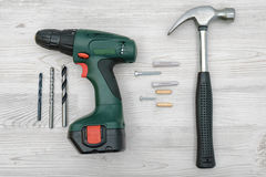 一把锤子、一个无绳的钻子有一套的位,几个螺杆、定缝销钉和插座在白色木背景 库存图片