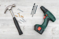 一把锤子、一个无绳的钻子有一套的位,几个螺杆、定缝销钉和插座在白色木背景 图库摄影