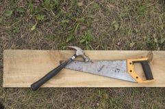 一把锤子和一把引形钢锯在一个木板 免版税库存图片