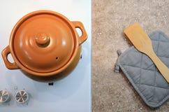 一把陶瓷罐、握持热锅的布垫子和小铲的顶视图 平的位置 图象 免版税库存图片
