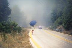 一把雨衣和伞的年轻女性在雾的路 雨衣的搭车在雨中的妇女旅行  图库摄影