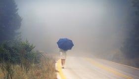 一把雨衣和伞的年轻女性在雾的路 雨衣的搭车在雨中的妇女旅行  免版税图库摄影