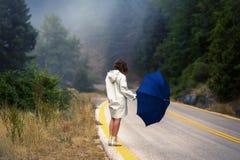 一把雨衣和伞的年轻女性在雾的路 雨衣的搭车在雨中的妇女旅行  库存图片