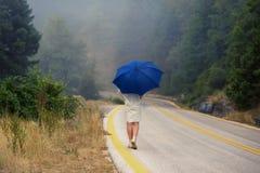 一把雨衣和伞的年轻女性在雾的路 雨衣的搭车在雨中的妇女旅行  免版税库存照片