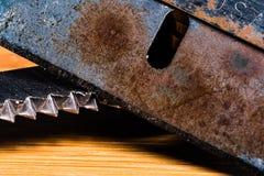 一把非常老,愚钝和生锈的剃刀的一个宏观图象有一把平等地肮脏和使用的被加锯齿的刀片的 免版税库存照片